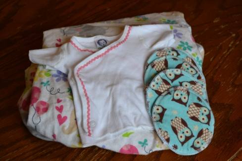 The flannel sheet I sewed, 2 sets of nursing pads, and a newborn side snap shirt where I sewed on baby rick rack.